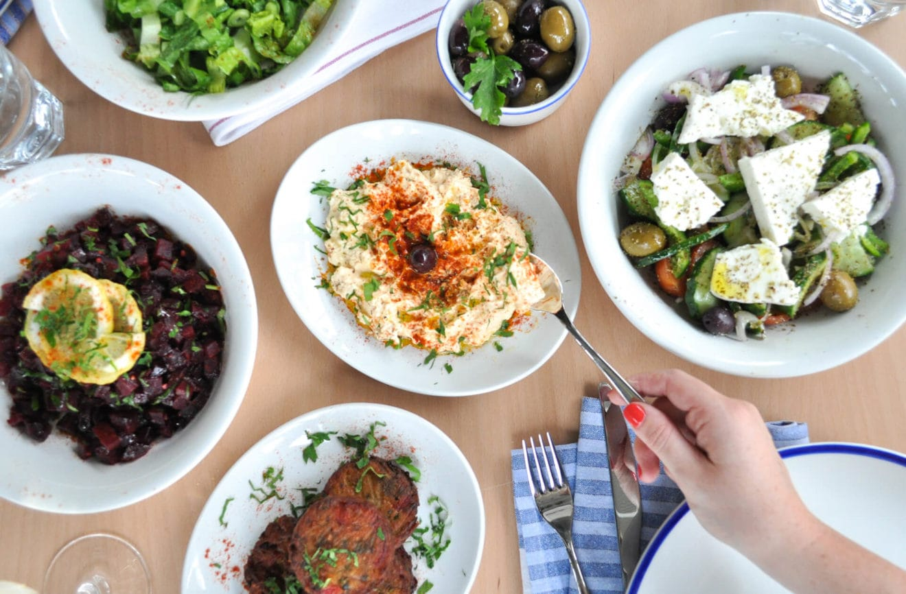 A table with various dishes of Greek food