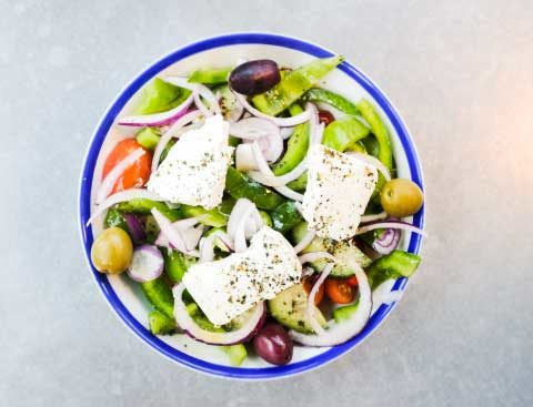 Fresh Greek salad in a bowl shot from above.