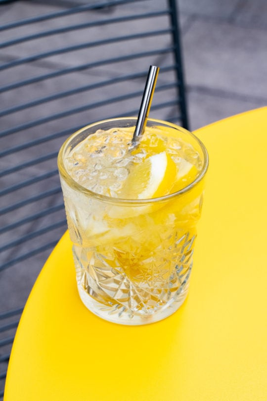 A gin and tonic cocktail on a yellow table